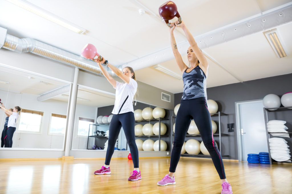two-women-trains-with-kettlebells-at-fitness-gym